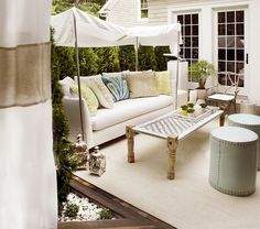 chic deck patio with blue gray ottomans with nailhead trim, sofa, Moroccan lanterns, branch chair and green blue sand outdoor pillows