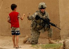 Soldier offers a fist bump to an Iraqi child while on patrol.