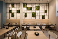 Reforma cafetería en Barcelona. Zona de mesas decorada con una pared módulos de jardines verticales. Diseño: Carolina Luzón y Luis Ruiz. Obra: Standal #reformas #locales #coffeeshop #interiordesign #verticalgarden