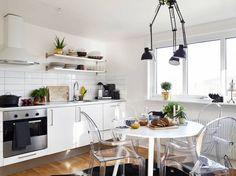 czarna lampa z trzema wysięgnikami w kuchni nad stołem,transparentne przeźroczyste krzesła w kuchni,przexroczyste bezbarwne krzesła w kuchni,okragły biały stół do kuchni w stylu nowoczesnym,nowoczesny okragły stół biały