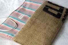 Hecho de un saco de arpillera reciclados café, este embrague respetuoso del medio ambiente cuenta con un botón marrón y cierre de abrigo de cordón de cuero. Forrado en una lavanda, rosa, blanco y turquesa raya impresión. Mide 11,5 x 5.5.