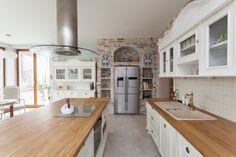 Große weiße Landhausküche mit Mauer und Holz Theken