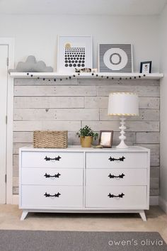 pallet planks on the wall behind crib. She white washed the wood & added a white shelf to display artwork in her baby boy's room.