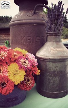 Sweet decor.... Antique milk containers engraved with the family name are used at this wedding as vases to display flowers.