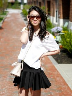 White off the shoulder tee, black fit and flare skirt, light pink crossbody purse