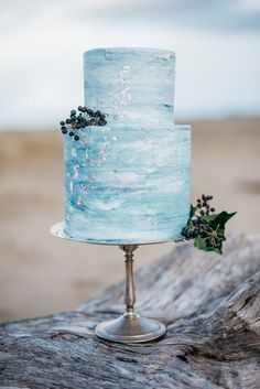 A light-turquoise-blue watercolor cake peppered with silver foil and berry clusters mirrors a wispy sky for a dreamy look.