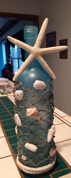 Enjoy a bottle of wine, remove label and wash.  Spray paint with sea glass frost paint, glue on shells and rope…. add lights and your done!!