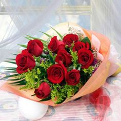 10 red roses, matched with greens, light orange package.