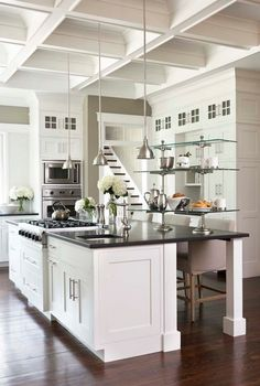 This white kitchen is modern, yet classic. The island is about 9′ long. Cooktop is by Viking and the fridge is the GE Monogram. Counters are honed absolute black granite.