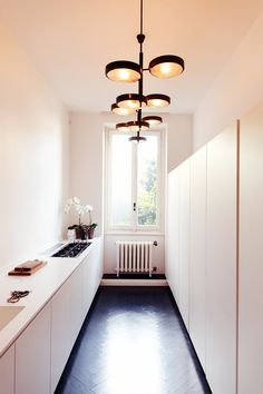Hello, gorgeous black herringbone wood floors, sexy Italian light fixture, and barely-there stovetop. We don't believe we've seen a more enigmatic kitchen.