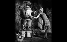 "1965: Model wearing dress designed by Sue Webb for Pixie of California poses with the robot ""B-9″ on set of television show ""Lost in Space."""