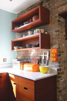 A wood cabinet kitchen that actually looks nice. floating shelves, exposed brick wall and yellow and orange accessories. Kitchen Shelf Unit, Wood Kitchen Cabinets, Shelf Units, Open Cabinets, Kitchen Reno, Kitchen Ideas, French Furniture, Wooden Furniture, Home Furniture