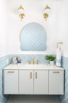 Beautiful light blue and white bathroom with bright brass accents, designed by Emily Henderson.