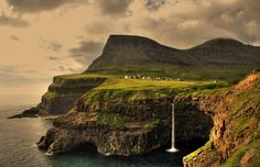 Gásadalur Village in the Faroe Islands has a population of 17 people. The Faroe Islands are under the sovereignty of the Kingdom of Denmark, situated between the Norwegian Sea and the North Atlantic Ocean, approximately halfway between Norway and Iceland. Places To Travel, Places To See, Places Around The World, Around The Worlds, Magic Places, Riomaggiore, Les Cascades, Beaux Villages, Landscape Wallpaper