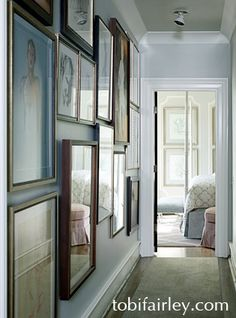 Gallery wall in hall; serene design by Tobi Fairley