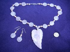 This oversized carved leaf pendant from China hangs from a necklace of matching rose quartz seashell beads and pale pink cultured freshwater pearls, punctuated with sterling silver Bali-style beads. This 20 inch necklace is hand knotted on pink cord and finished with a sterling silver