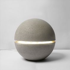 Petite Gayalux  Matière/materials : béton brut/concrete    The Gayalux lamp is both sculptural and light. This ball mineral is anchored on the ground, it seems to levitate with his streak of light passing through it. Concrete leaves architecture for the object, the block is curved like a skin.