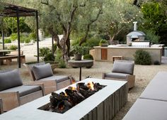 Beautiful back yard with modern fire pit and outdoor kitchen. best of all, minimal yard maintenance in this set up!