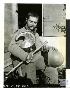 """""""Anzio, Italy! Holding an ancient Roman Helmet [possibly a Napoleonic era helmet] in one hand and his own 20th century head gear in the other, Capt. Frederick J. Saam, of Calumet, Mich., presents a contrast in two distant epochs of war which the antique town of Anzio has witnessed."""" Anzio, Italy. 31 January 1944. (US Signal Corps photo, via National WWII Museum)"""