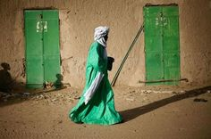 A Malian man dressed in green walks between green doors of closed shops in Gao, northern Mali.