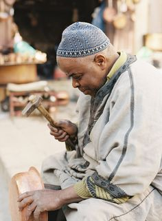 Metal-working artisan Hamid with his tools and copper pot