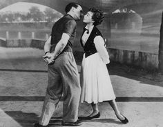 "Gene Kelly and Leslie Caron steal a kiss along the Seine in ""An American in Paris"""