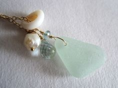 """Kahili Creations  Sea Glass necklace with aquamarine, puka shells and pearl - Kai Malie  This necklace is reminiscent of walks along Hawaiian beaches. A frosted nodule of sea foam green sea glass is the centerpiece, joined by a puka shell, ivory rosebud pearl, and aquamarine gemstones. The gold-filled necklace sparkles like sunlight on a thousand tiny waves.    Necklace is 25"""" long and sea glass piece measures 3/5"""" (16.4mm) long."""