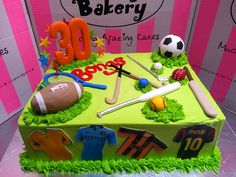 A4 Wicked Chocolate cake iced in green butter icing, decorated with 3D Sport themed designs - rugby ball, hockey stick, golf club, tennis racket, softball bat, cricket bat, soccer ball - & edible photos of soccer jerseys on sides, 3D #30 by Charly's Bakery