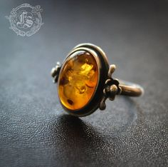 Pretty little ring with a gorgeous, glowing profile. A domed oval of genuine baltic amber is simply framed and flanked by two tiny flowers on each side. Will fit a size 6 1/2 US or M UK and dates from the 1980s. It is unmarked by is most certainly silver. All my vintage jewellery is carefully sourced and refurbished by my partner Mike and myself in a converted 18th century naval school on the wild North coast of Scotland.