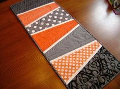 """Add some modern flair to your decor with this lively table runner. The colors are bright and the pattern is bold. The white accents are topped stitched onto the piece which gives it great texture. This table topper measures 12"""" x 31.5"""" - a really nice size to decorate the dining room or coffee table. The fabrics in this piece are modern and very fun. It is quilted with simple straight line quilting in a white cotton thread. A bright orange scrolled fabric is found on the back."""