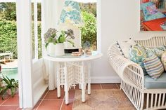 A small white end table with an east Asian flair holds small knick-knacks that show the owners' personality and a wicker lamp with a customized, fabric-covered shade. The white painted walls and Mexican tile floor give the space an always-fresh look that feels uncluttered — even with so many accessories.