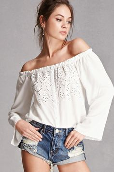 A crinkled woven off-the-shoulder top by Honey Punch™ featuring an crochet eyelet front, an elasticized neckline, button front closure, and long bell sleeves.
