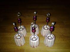Naamkaarthouders ui gips. Siliconen bakvormpjes dienen als vormpjes. Bovenaan het stokjes soldeer je een klein stukje van een soepele veer om je kaartje te klemmen. Kleuren met glitterlijm :-)