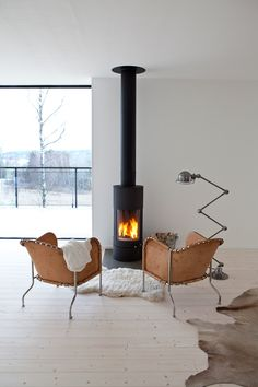 A tiny fireplace in the middle of an all-white living room. Animal furs, wide slat white wood floors - I'm in love. Home Fireplace, Fireplace Design, Small Fireplace, Fireplace Ideas, White Wood Floors, Wood Flooring, Easy Flooring, Wood Paneling, Hardwood Floors