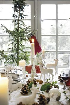 table setting: love the white deer; candles; simple tree; holly leaves; mercury glass candle sticks