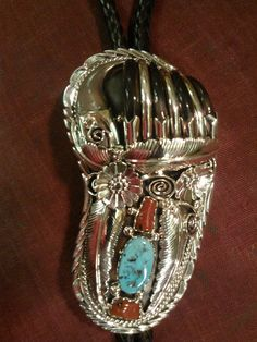 Sterling Silver Turquoise and Coral Bear Claw Bolo Tie  Sterling Silver bolo tie with 5 real Bear claws separated by silver wire and mounted in a bolo. The pattern in this beautifully handcrafted bolo has feathers, flowers, lariats, and vines. The stones are Sleeping Beauty turquoise and red coral.