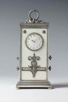 A large Imperial guilloché enamelled desk clock and calendar by Carl Fabergé, of rectangular upright form, enamelled translucent opalescent oyster white over a guillochage, centred to the top by a circular pearl set bezel, containing beneath glass an opaque white enamel dial with Arabic chapters and openwork gold hands, the apertures for the calendar rolls enamelled in French with the months, days of the week and date flanking a flaming silver torch entwined by laurels, surmounted by a la