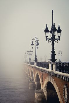 Misty romance in France. Lanterns on a stone bridge in the Fog