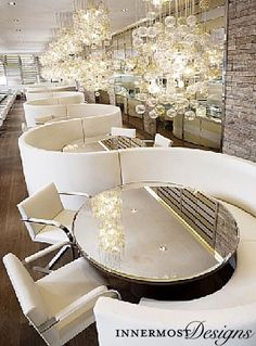 The mirrored tops on the tables reflect the beautiful chandelier to increase the light in the room. The connected chair backs create a flow in the restaurant.