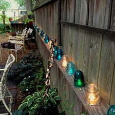The Best 21 DIY Lighting Ideas for Summer Patio and Yard Decorate the garden fence with glass insulators that are lit underneath with a string of solar powered LEDs. Insulator Lights, Glass Insulators, Backyard Lighting, Outdoor Lighting, Outdoor Decor, Lighting Ideas, Fence Lighting, Lighting Design, Rope Lighting