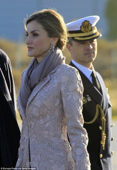 Letizia added a touch of glamour with dangling silver earrings and a chignon hair style...