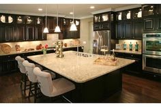The upper level of lighted, glass front cabinets create a jewel-like display in this sophisticated black and taupe kitchen. From Standard Pacific Homes, on Lake Wylie, near Charlotte, NC. Taupe Kitchen, New Kitchen, Kitchen Dining, Kitchen Ideas, Kitchen Reno, Kitchen Inspiration, Kitchen Designs, Kitchen Storage, Dining Area