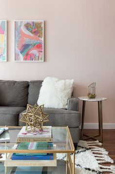 Give your home the glamorous makeover it deserves with this trendy blush and gray  living room remodel from Carmen, of Camille Styles. Carmen offers you tons of DIY design inspiration, like this chic living room. Colorful wall art and gold accents are the perfect complement to the light pink hue of Life is a Peach in this stylish space.