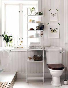 Toalettstol med träloch i ljust badrum med en steghylla för förvaring.