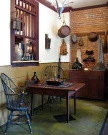 FARMHOUSE – INTERIOR – vintage early american farmhouse showcases raised panel walls, barn wood floor, exposed beamed ceiling, and a simple style for moulding and trim, like in this farmhouse with windsor  chairs.