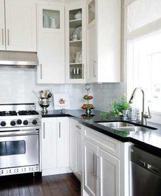 kitchens - black granite countertops white glass-front cabinets subway tiles hardware Laurel Ridge Homes - white kitchen cabinets, black granite