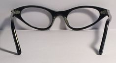 Vintage eyewear. Cat eye style. 1960s. Soft grey with rhinestones on frame front. No missing rhinestones. Back of frame and temple are gloss black. This color combination makes for a stunningly beautiful pair of eyewear! Frame is in great condition. High quality and ready for your prescription or non-prescription lenses. Eye size 46mm. Bridge size 16mm. Temple length 135mm. Measurement across frame front 5 1/3 inches. Frame depth from top to bottom 33mm. I ship USPS Priority, insured with…
