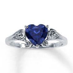 A heart-shaped, lab-created sapphire bordered by swirls of 10K white gold forms the elegant centerpiece in this romantic ring for her. Diamond accents enliven either side of this fine jewelry ring.