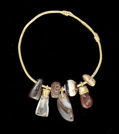 A Roman gold and hardstone amuletic bracelet. Eastern Empire, circa 1st-3rd Century A.D. -  The gold bracelet in the form of a bangle, oval in section, each end wound spirally along the hoop, with seven amulets or beads, including an amber bead, a carnelian phallic pendant with gold mount, a spherical banded onyx bead, a pointed agate pendant suspended from a gold loop, an amber bead with drilled detail, a rock crystal pendant with gold mount, and a haematite pendant. | © Bonhams 2001-2014