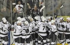 The Kings, and one of their fans, celebrate the 2-1 overtime victory against the New Jersey Devils in Game 2 of the Stanley Cup Final on Saturday night at the Prudential Center in Newark, N.J.
